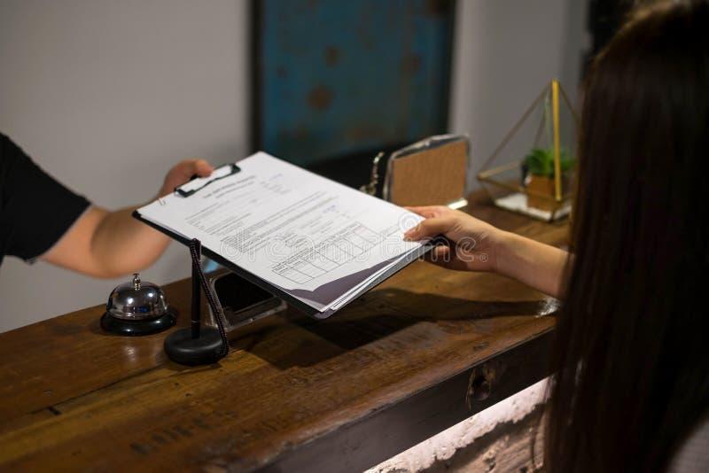 Recepcionista enviado os documentos ao convidado para assinar e encher-se acima do processo do registro do formul?rio Conceito do foto de stock