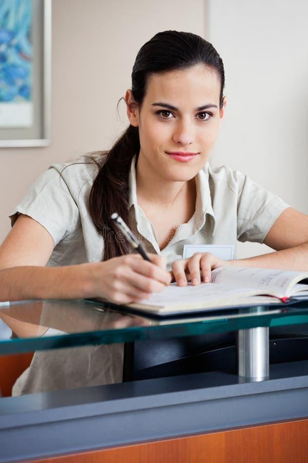 Recepcionista fêmea Writing In Book fotos de stock