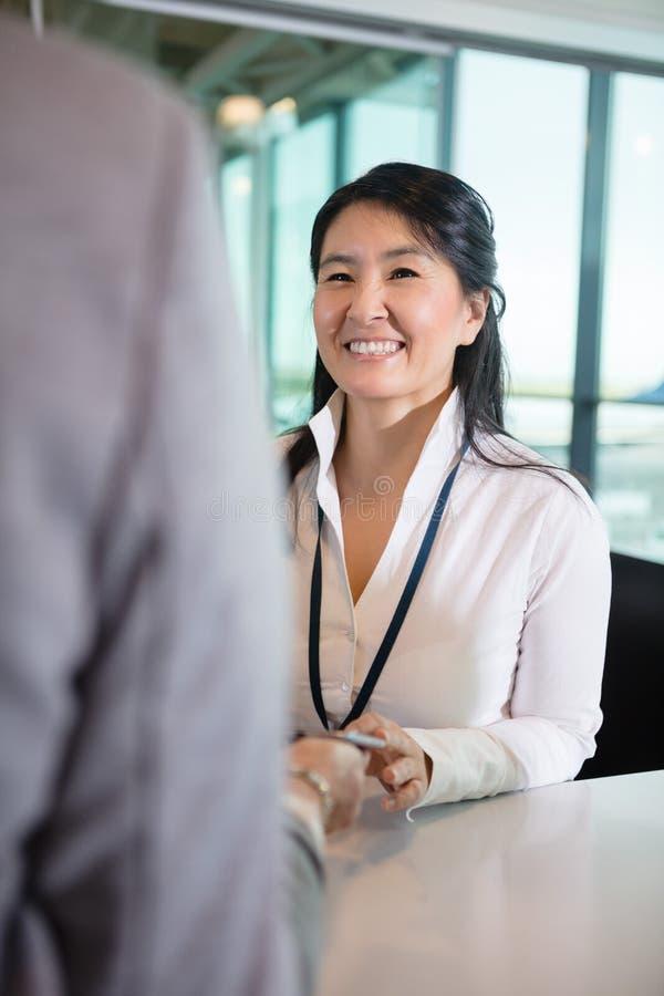 Recepcionista feliz Looking At Businesswoman no contador do aeroporto foto de stock royalty free