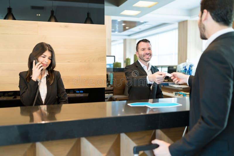 Recepcionista Giving Card Key ao homem de negócios At Lobby foto de stock royalty free