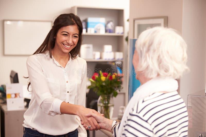 Recepcionista Greeting Female Patient en la clínica de la audiencia fotografía de archivo