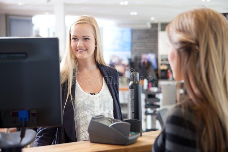 Recepcionista Helping Customer en el salón de belleza fotografía de archivo