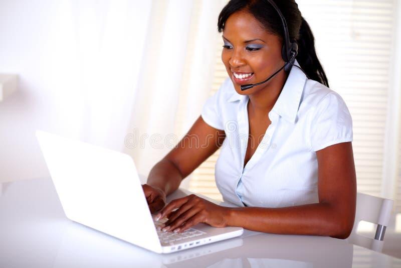 Recepcionista joven encantador que trabaja en la computadora portátil imagen de archivo libre de regalías