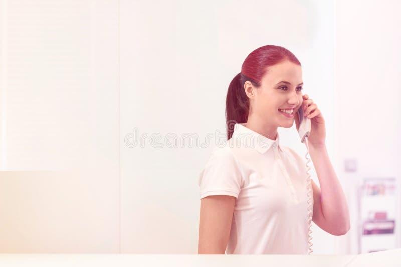 Recepcionista joven sonriente que habla en el tel?fono en el contador del pago y env?o fotos de archivo