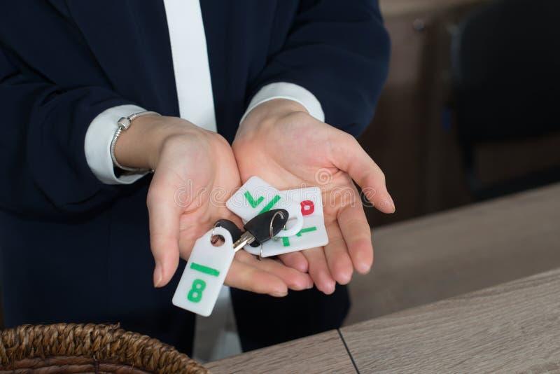 Recepcionista na recepção da pensão que mostra chaves com dígitos ao convidado ou ao cliente imagens de stock