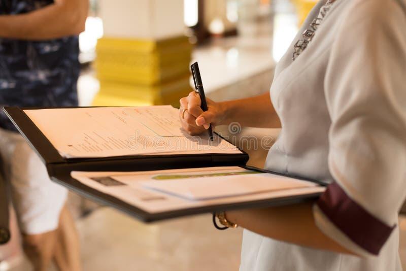 Recepcionista que enche-se no formulário de inscrição fotografia de stock royalty free
