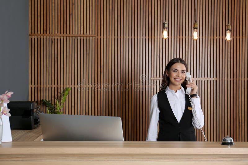 Recepcionista que habla en el teléfono en el escritorio imágenes de archivo libres de regalías