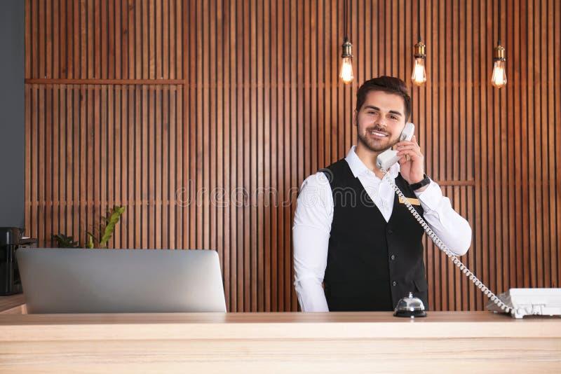 Recepcionista que habla en el teléfono en el escritorio fotos de archivo libres de regalías
