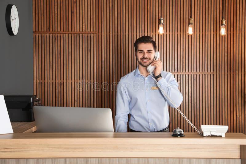 Recepcionista que habla en el teléfono en el escritorio imagenes de archivo