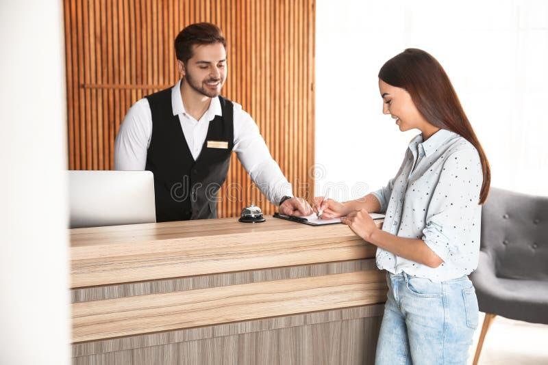 Recepcionista que registra al cliente en el escritorio imagen de archivo