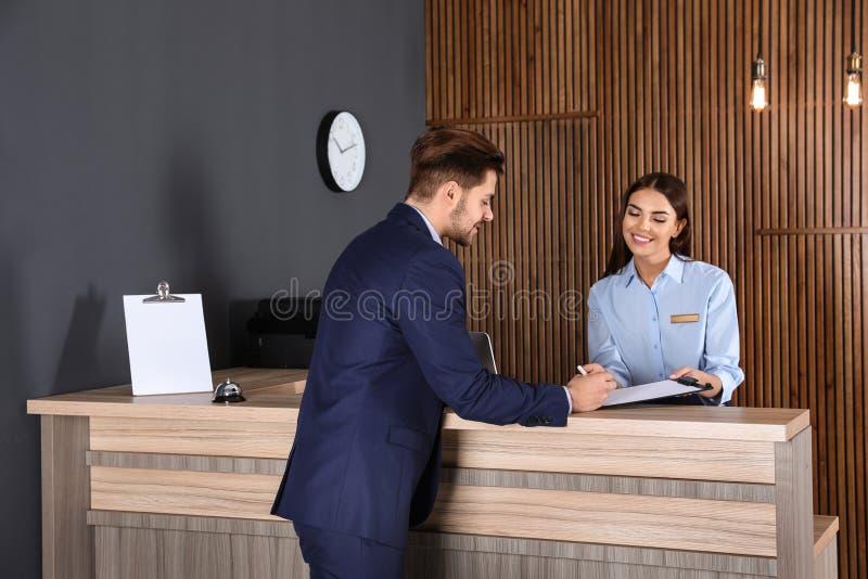Recepcionista que registra al cliente en el escritorio fotos de archivo libres de regalías