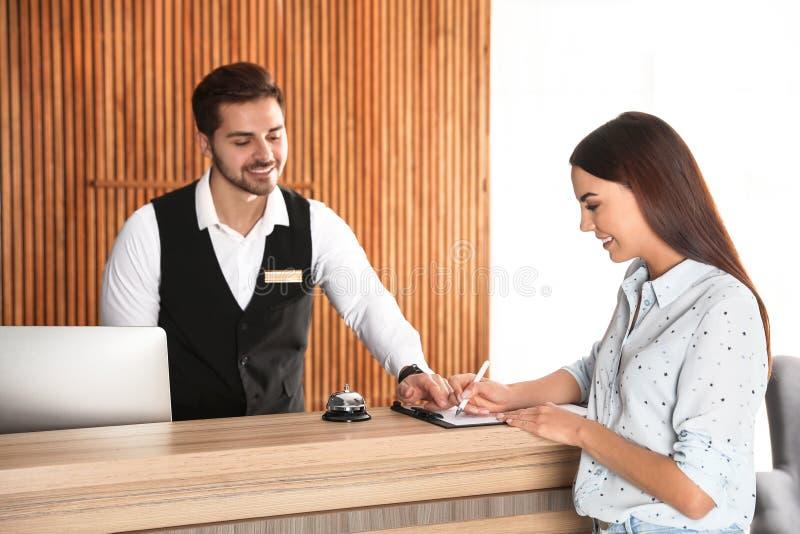 Recepcionista que registra al cliente en el escritorio fotos de archivo