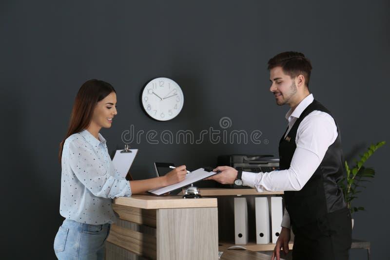 Recepcionista que registra al cliente en el escritorio fotografía de archivo