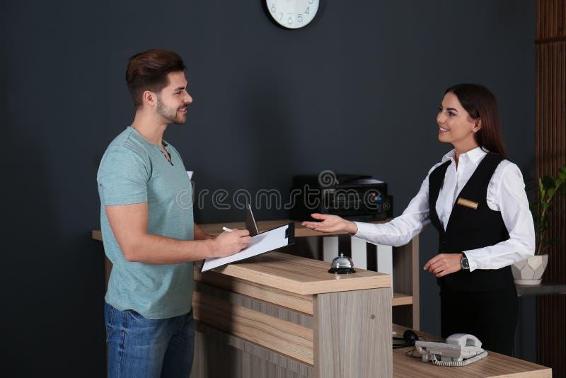 Recepcionista que registra al cliente en el escritorio fotografía de archivo libre de regalías