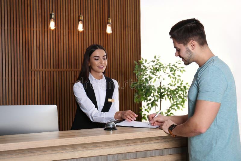 Recepcionista que registra al cliente en el escritorio foto de archivo