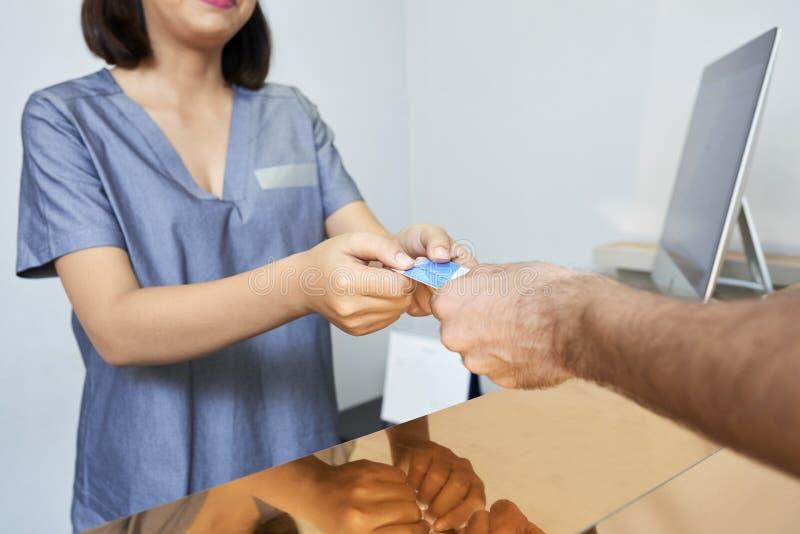 Recepcionista que toma o cartão de crédito imagem de stock