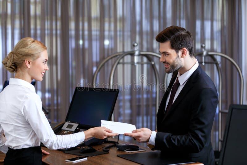 recepcionista sonriente que da el sobre al hombre de negocios imagen de archivo libre de regalías
