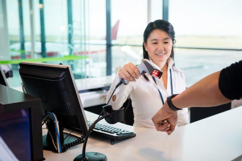 Recepcionista sonriente Scanning Smart Watch del pasajero en Airpor imagen de archivo