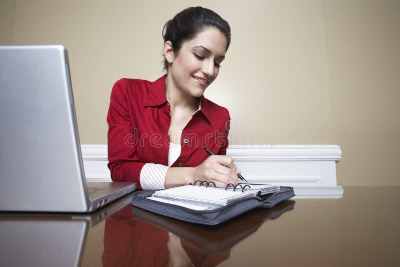 Recepcionista Writing In Diary foto de archivo libre de regalías