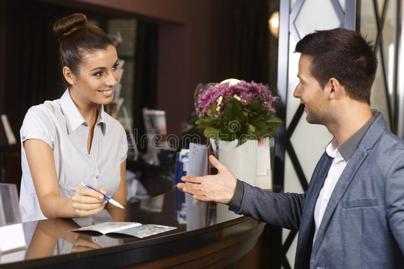 Recepcionista y huésped en el hotel foto de archivo