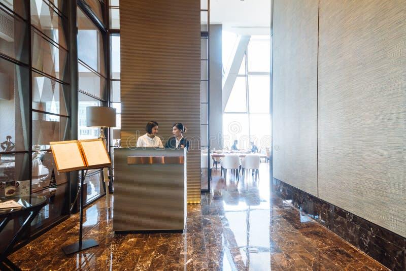 Recepcionistas do hotel na frente do restaurante decorado moderno no hotel imagem de stock