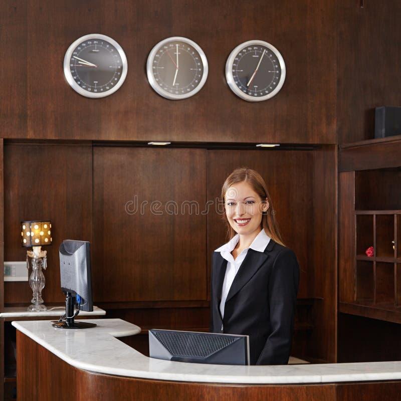 Recepcjonista za kontuarem przy hotelem obraz stock