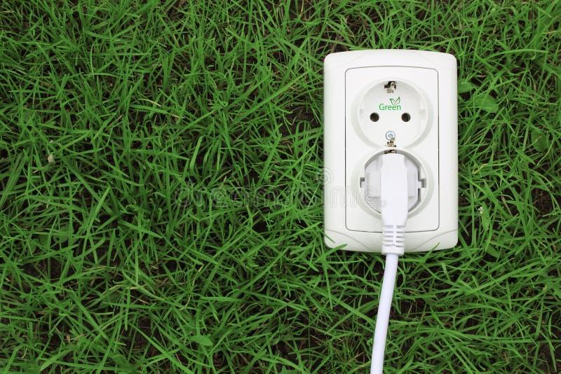 Receptáculo de la energía eléctrica en una hierba verde fotos de archivo