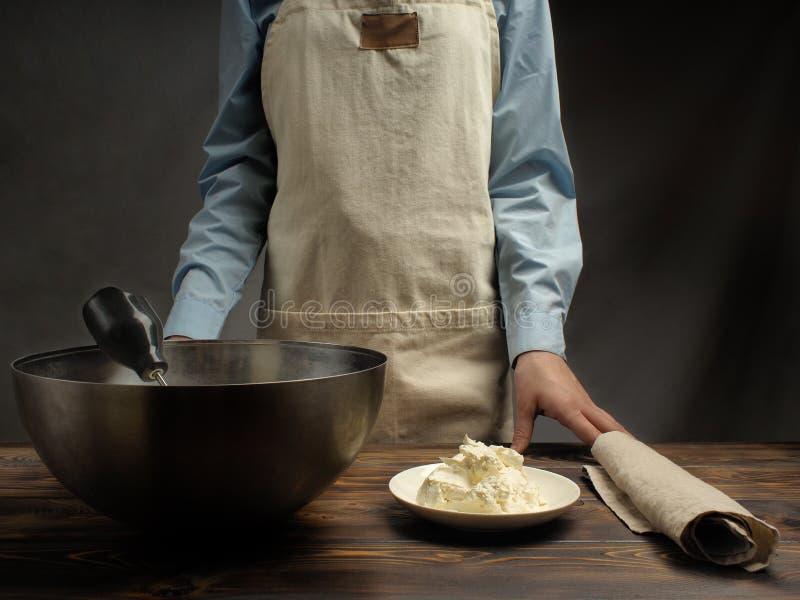 Recept av att laga mat av tiramisuen, deltredjedel: 'Att blanda äggvikt med mascarpone ', arkivbild
