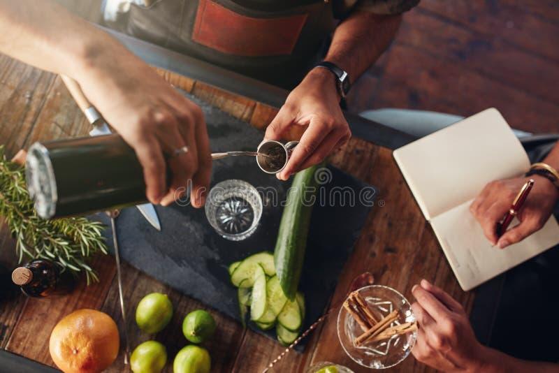 Recept van de twee barmannen het experimenterende nieuwe cocktail stock fotografie