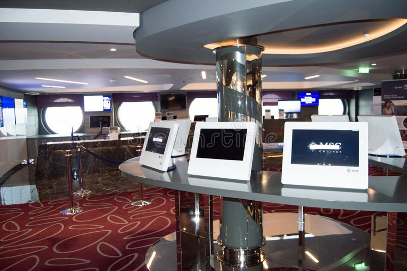The reception area of the cruise liner with views of the monitors and a tour Desk, MSC Meraviglia, 8 October 2018. The reception area of the cruise liner with royalty free stock images