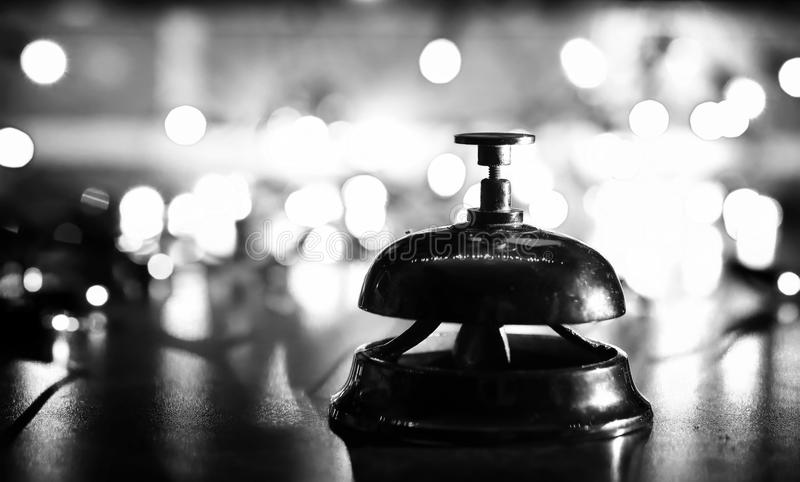 Reception bell on the table and shining garland background stock photos