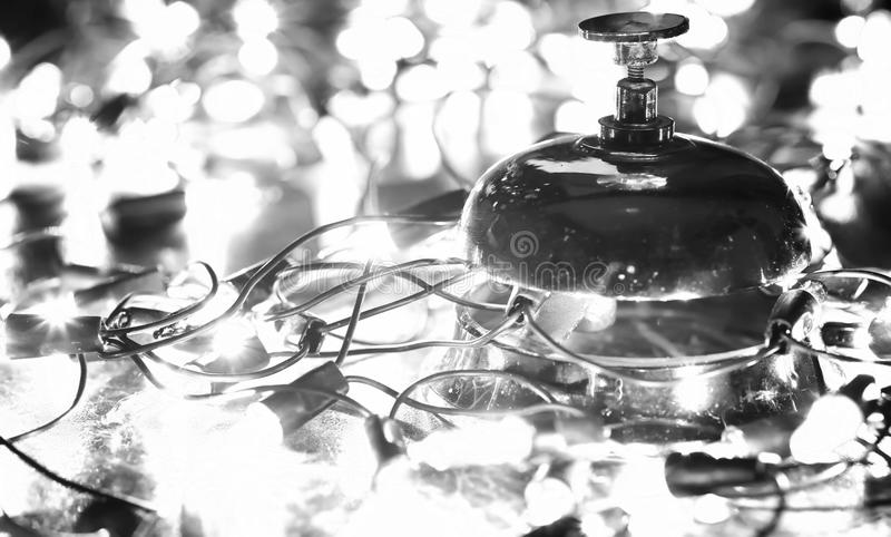 Reception bell on the table and shining garland background royalty free stock photography