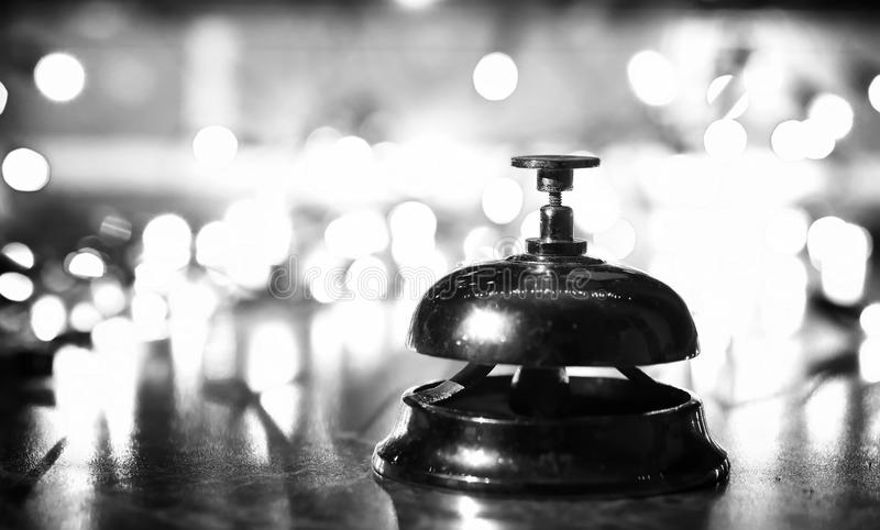 Reception bell on the table and shining garland background stock images
