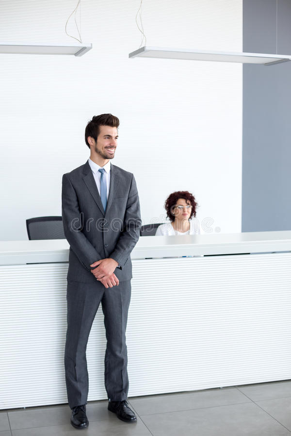 Reception guy is at service of passengers. Young reception guy is at service of passengers royalty free stock photo