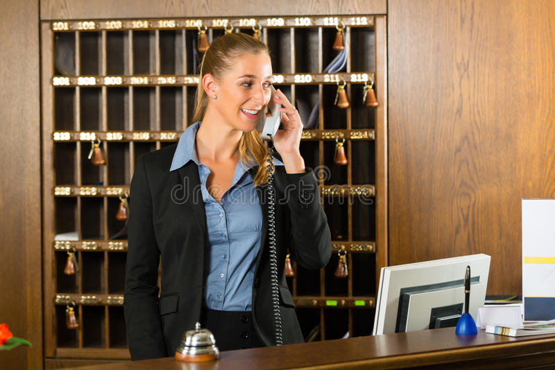 Reception of hotel - desk clerk taking a call. Reception of hotel, desk clerk, woman taking a call and smiling