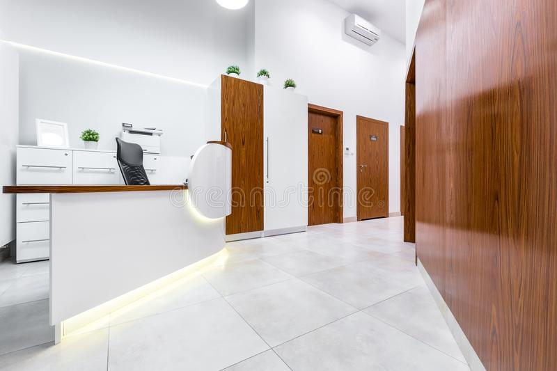 Reception of modern, private clinic. With white flooring, wooden doors and desk stock photo