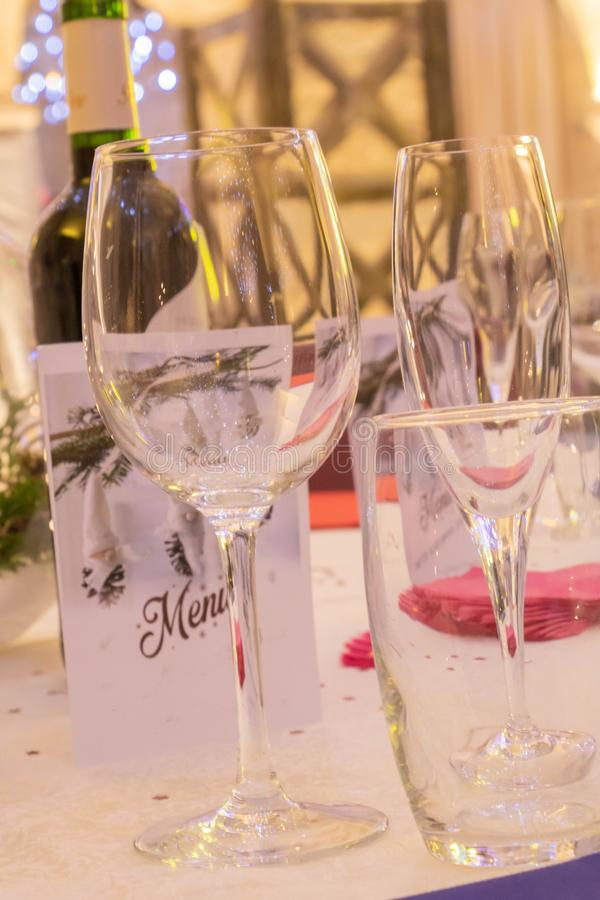 Reception and party table, with wine glass, water glass and champagne glass, menu and bottle of wine. Table, wineglass, and glass of champagne for big royalty free stock image