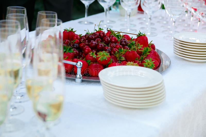 Reception table. Glasses of wine, champagne, plates and berries on the white tablecloth. Catering business. Reception table. Glasses of wine, champagne, plates stock images