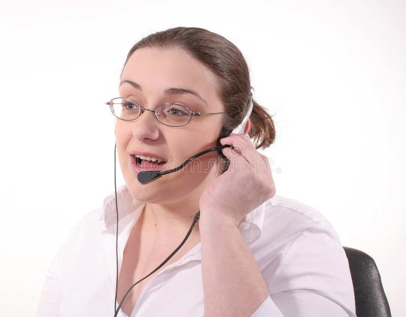 Receptionist. A young brunette woman speaking on the phone using a headset stock images