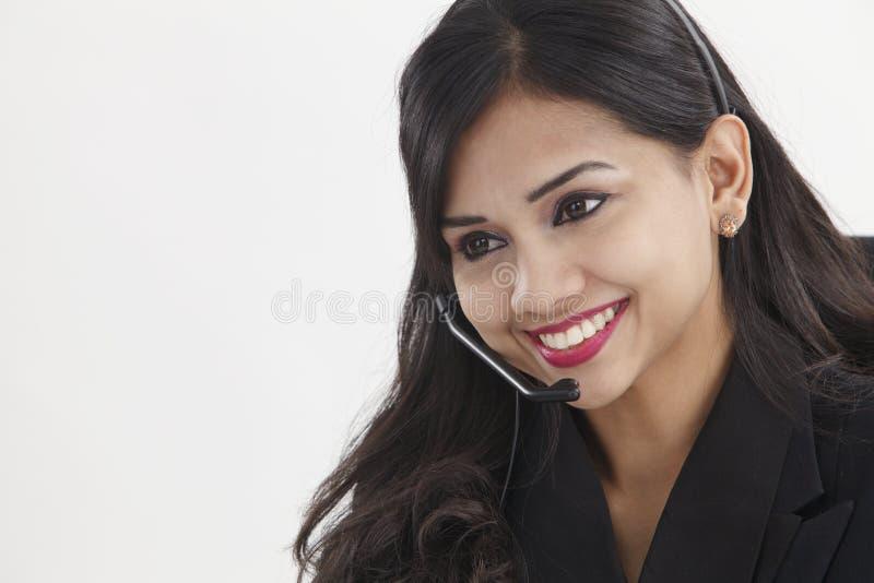 Receptionist. Beautiful receptionist wearing head set talking stock photography