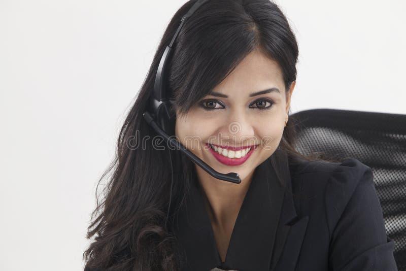 Receptionist. Beautiful receptionist wearing head set talking stock image