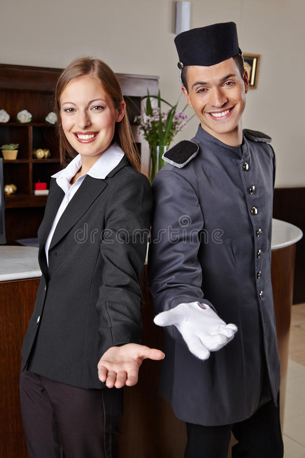 Receptionist and bellboy in hotel offering welcome. Smiling receptionist and happy bellboy in hotel offering a welcome stock photo