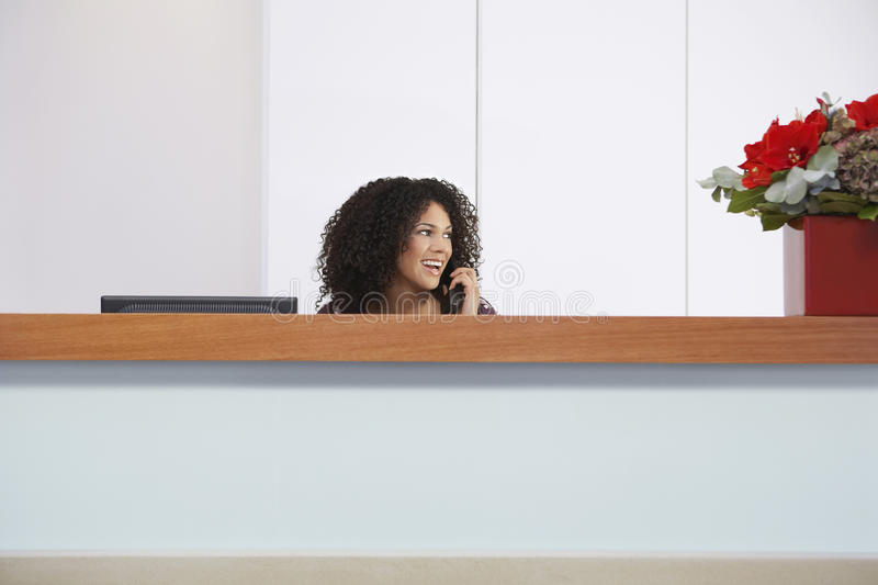 Receptionist On Call Behind Reception Desk royalty free stock photos
