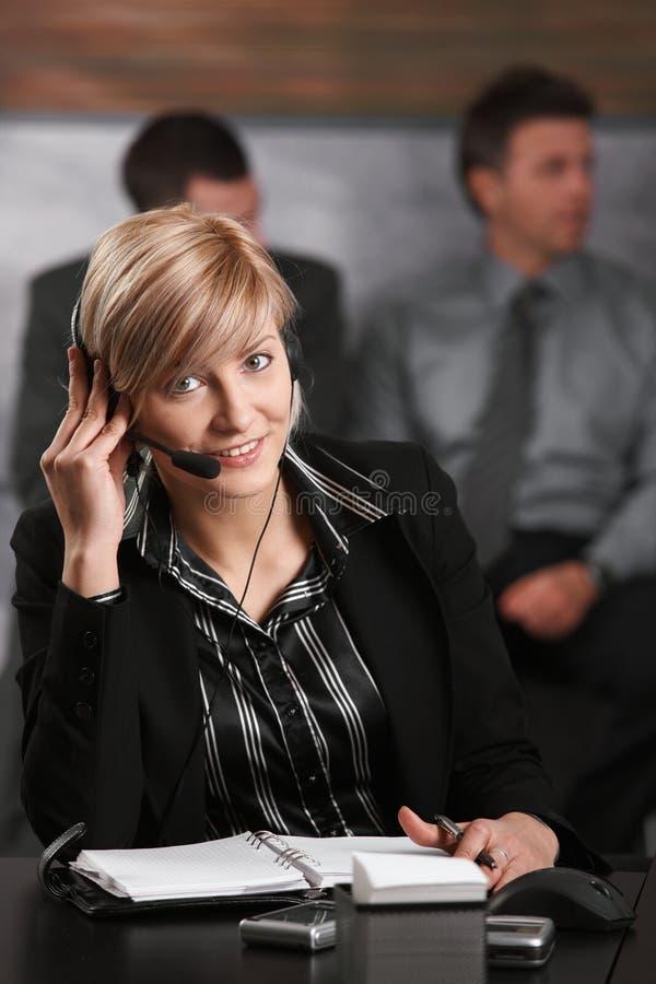 Receptionist che comunica sul telefono fotografia stock libera da diritti
