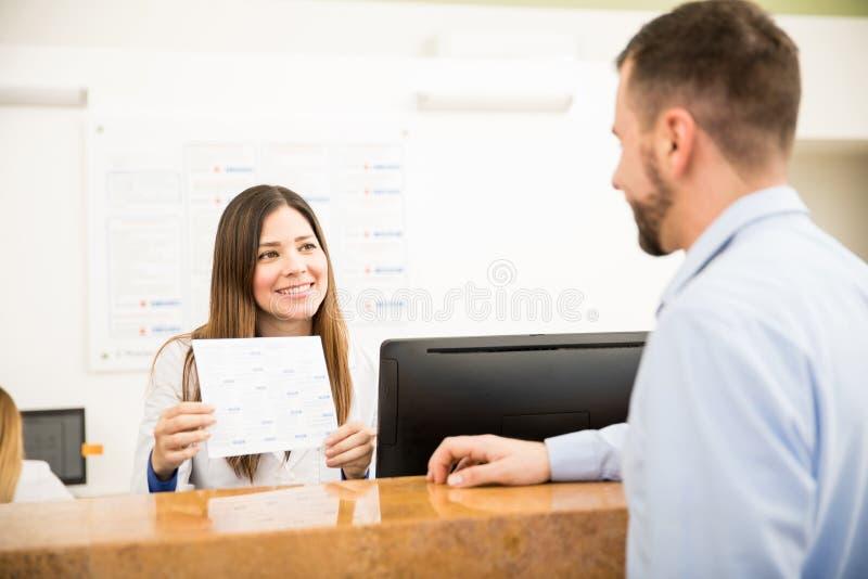 Receptionist che mostra i servizi ed i costi immagini stock