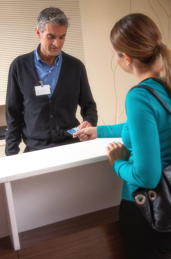 Receptionist e paziente che discutono circa il pagamento alla ricezione d immagini stock libere da diritti