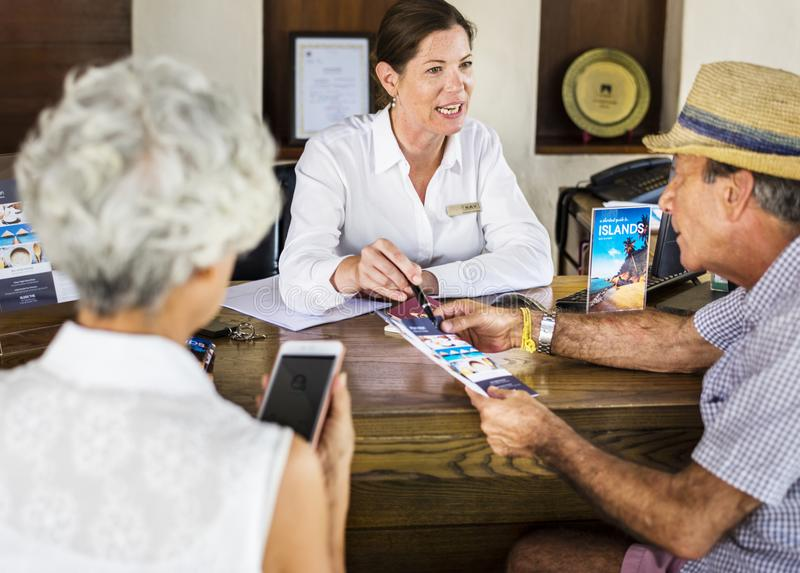 Receptionist giving explanations to a senior man royalty free stock photo