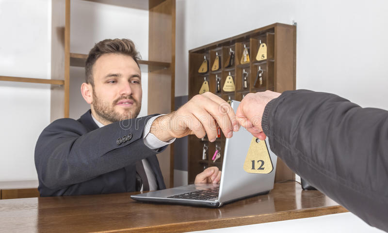 Receptionist Giving the Key. Image of a receptionist at his desk giving the key to a client. Selective focus on the key stock photography