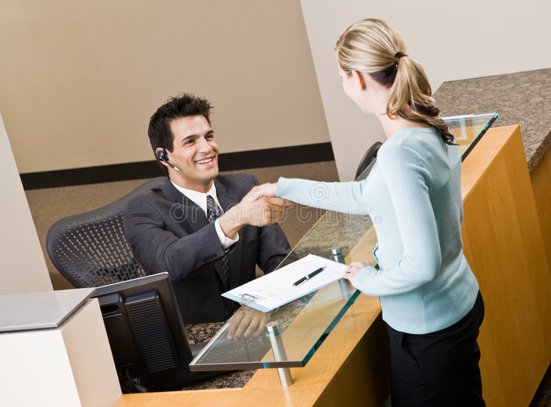 Receptionist greeting woman at front desk. Friendly receptionist greeting woman at front desk and shaking hands stock photography