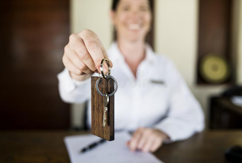 Receptionist handing room key to guest stock photo